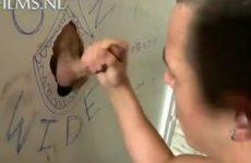 Hij pijpt de stijve lul door het gat van de muur
